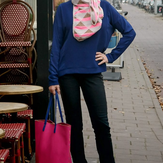 A blue sweater as a background for a pink scarf