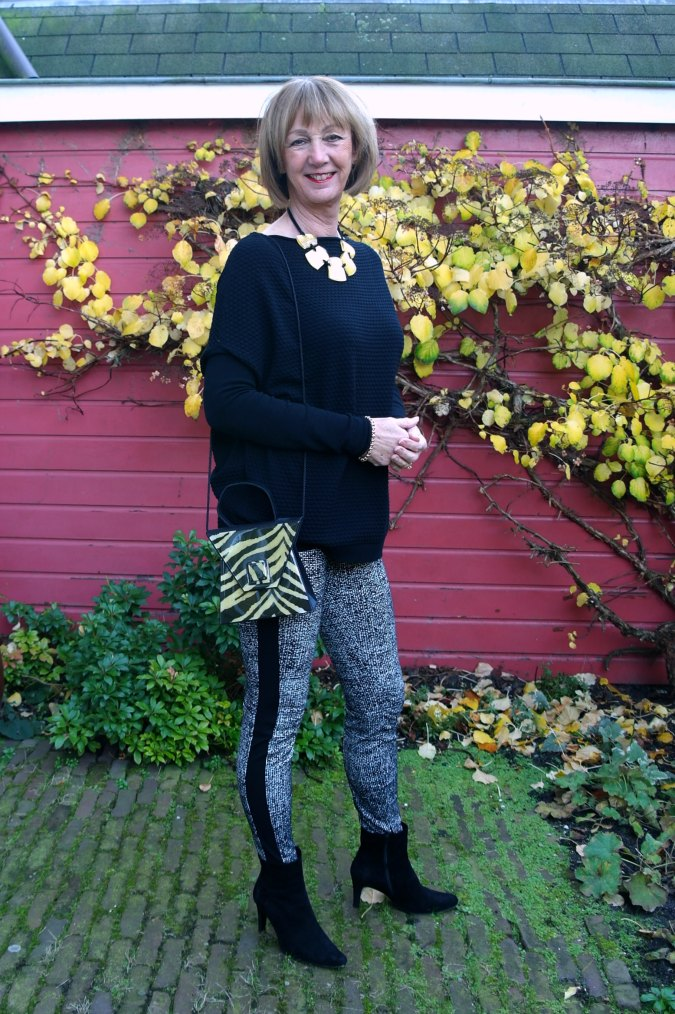 black and white treggings, black sweater and golden necklace.
