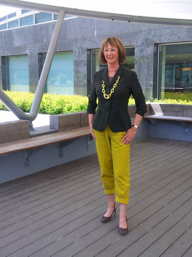 Yellow ochre trousers with green jacket and yellow chain necklace