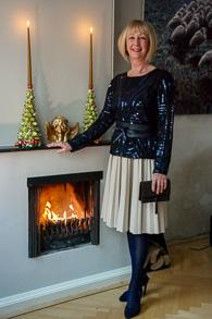 Blue sequined top, camel pleated skirt and blue suede pumps