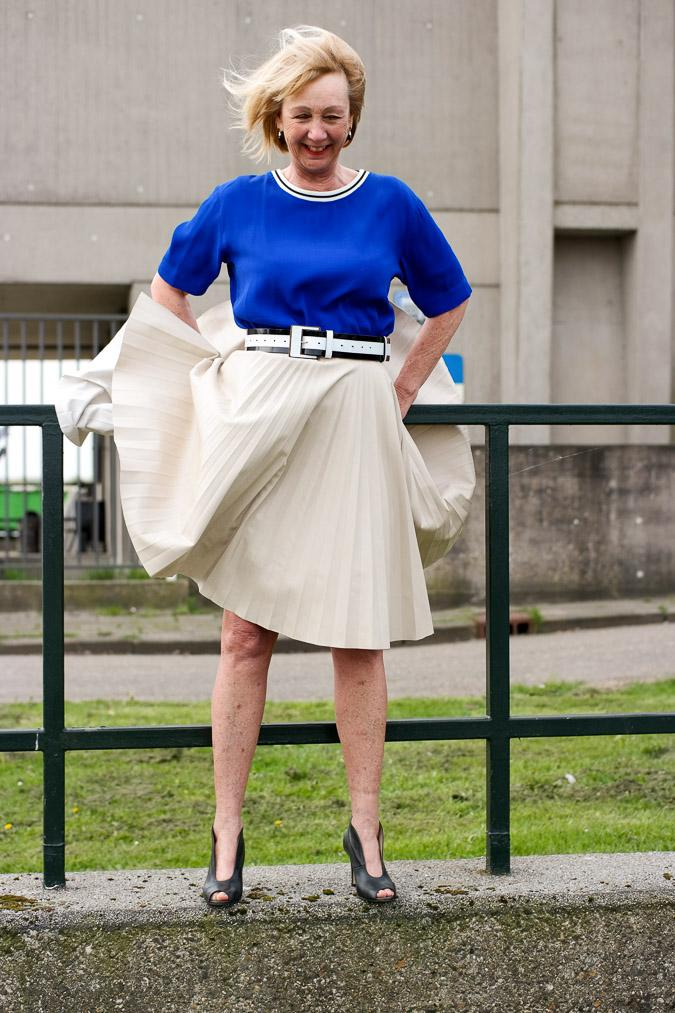 Bright blue top with a camel pleated skirt