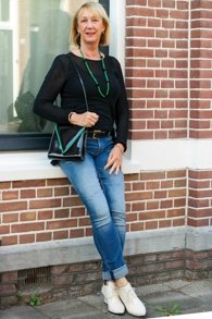 Black high low sweater, skinny jeans and patent leather mini bag