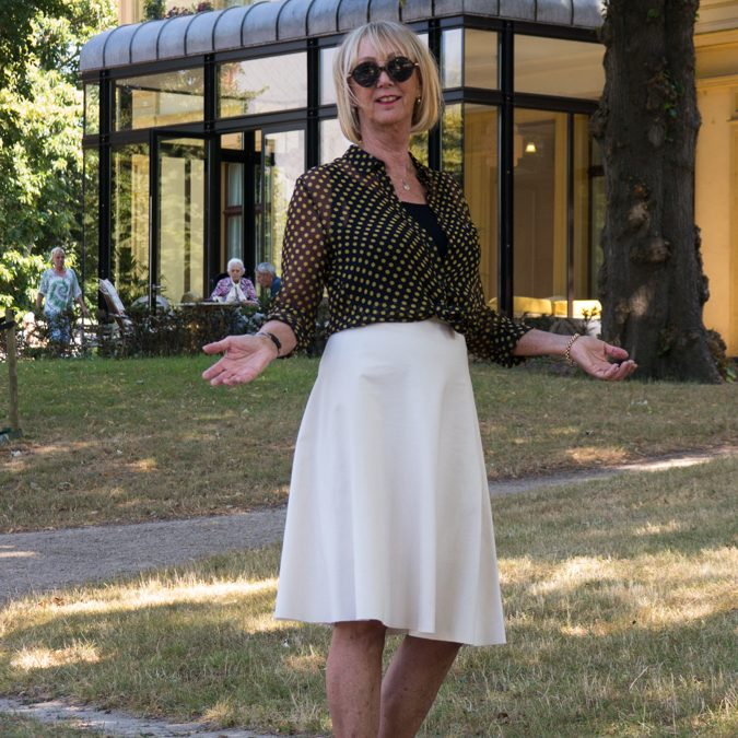 Wide cream skirt with black and yellow polka dot blouse