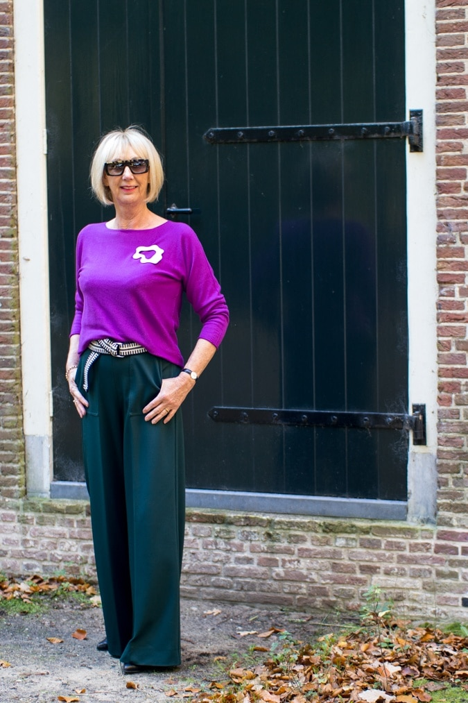 Wide green trousers with a purple jumper