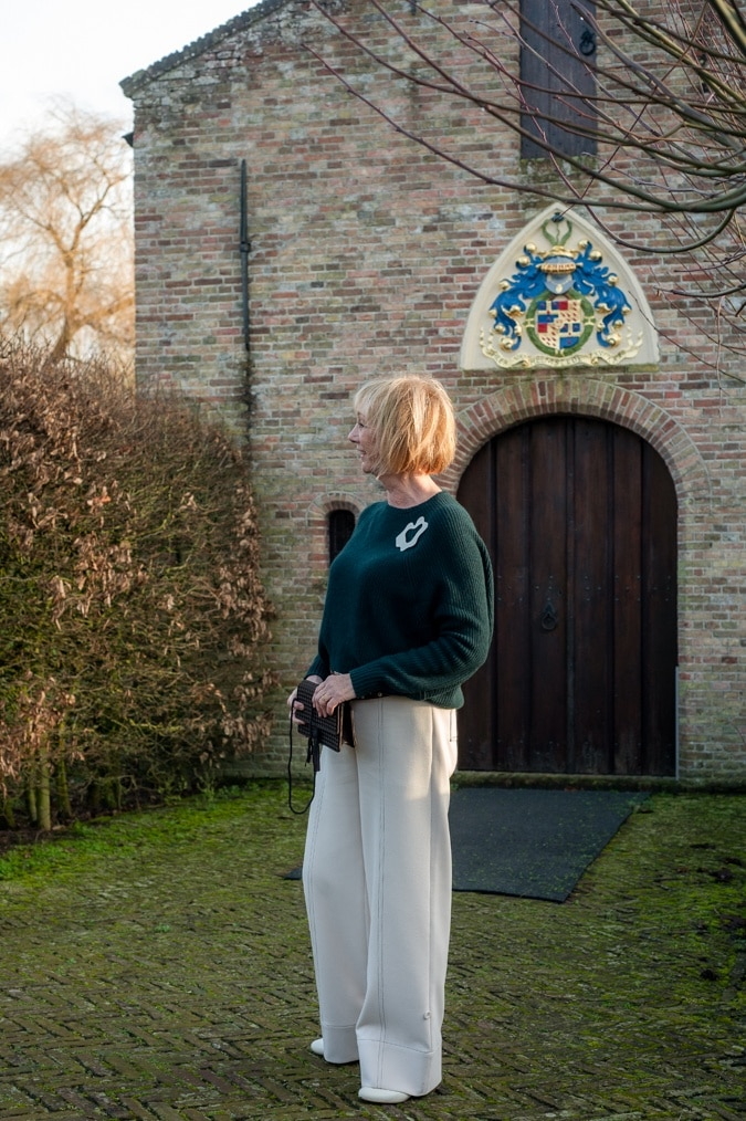 Dark green jumper and cream trousers