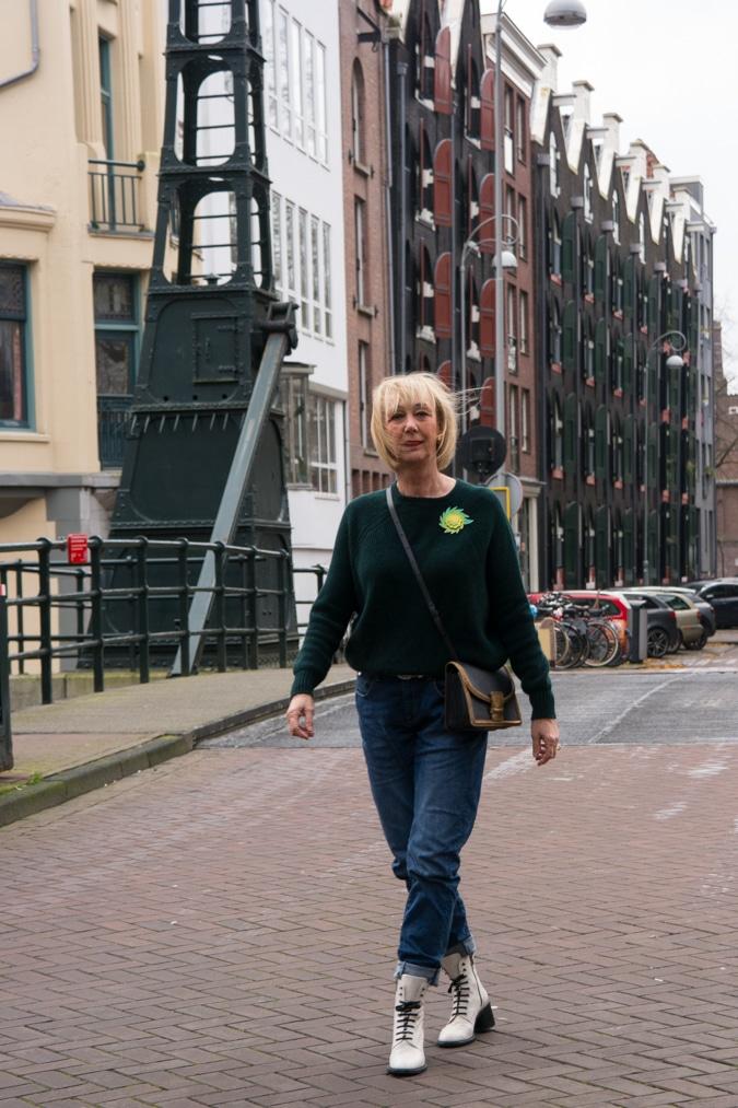 Dark green jumper with a light green brooch