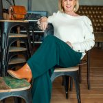 A cream jumper on wide green trousers