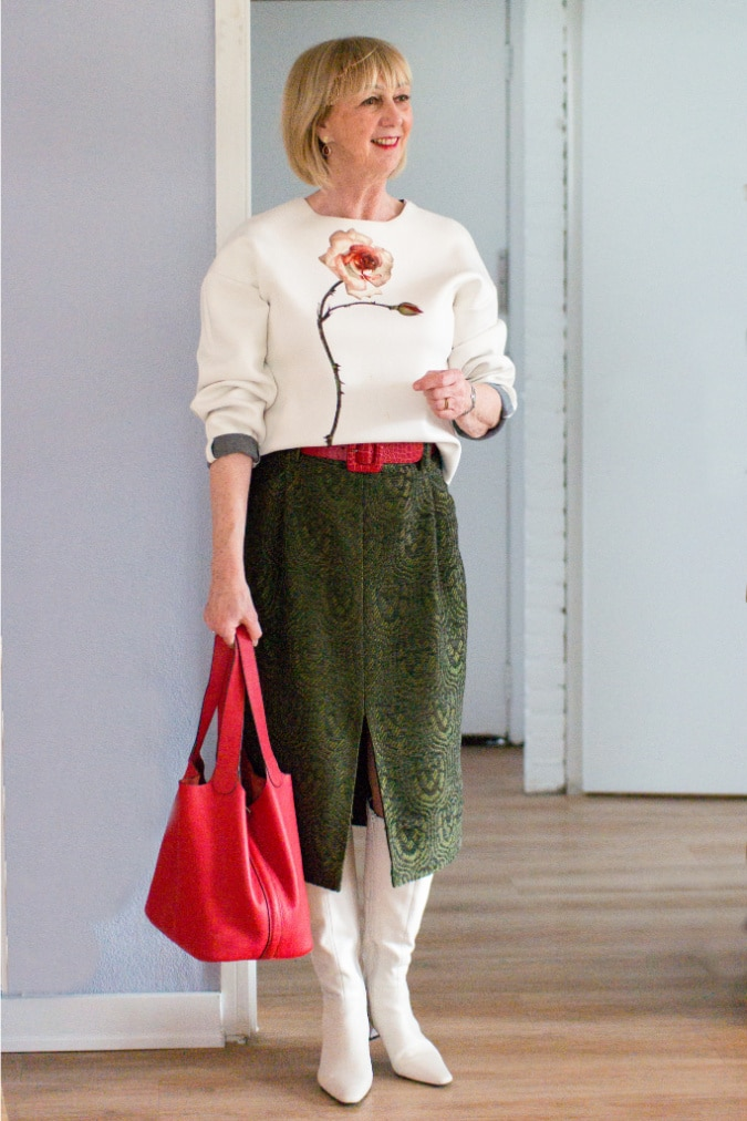 A green midi skirt with a cream sweater