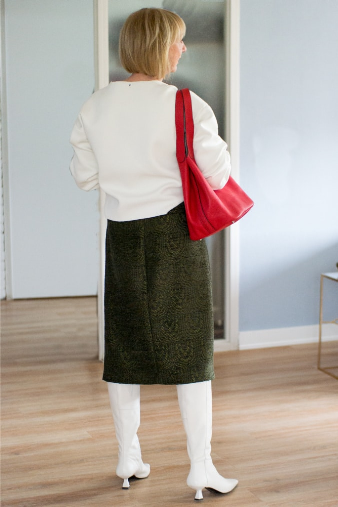 green midi skirt with a cream sweater