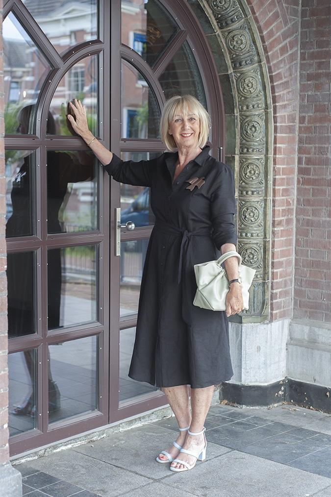 Black linen dress with golden brooch by Claudia Roskam