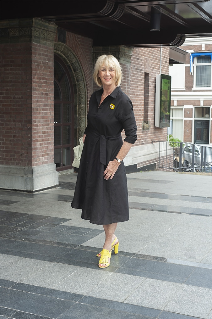 Black linen dress with yellow sandals and a yellow brooch