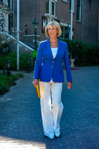 White flared trousers with a bright blue jacket